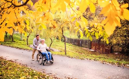 秋の自然の中車椅子で年配のカップル。