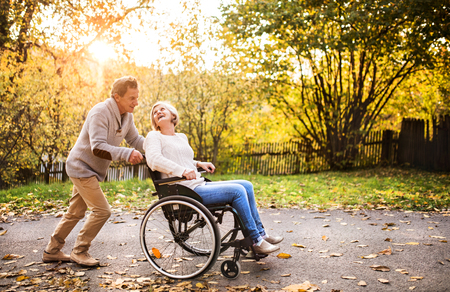 walking paths: Senior couple in wheelchair in autumn nature. Stock Photo