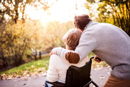 Hoger paar in rolstoel in de herfstaard.