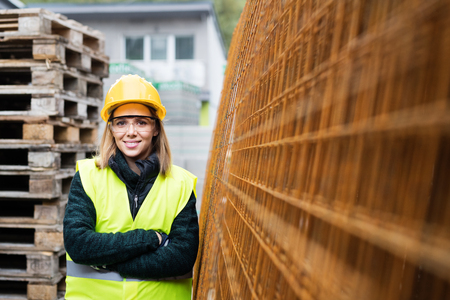 fil de fer: Young woman worker in an industrial area. Banque d'images