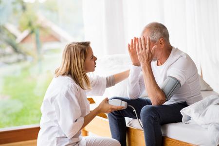 Visitante de salud y un hombre mayor durante la visita domiciliaria.