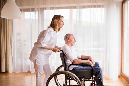 家の間に車椅子で看護師とシニアの男性をご覧ください。 写真素材
