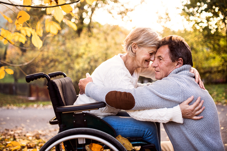 Senior couple in wheelchair in autumn nature. Stock fotó