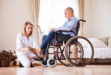 Infermiera e uomo anziano in sedia a rotelle durante la visita a casa. Archivio Fotografico - 89877140