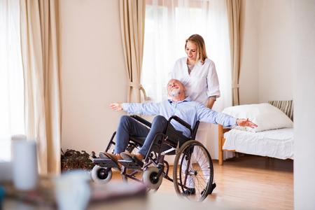 간호사와 가정 방문하는 동안 휠체어에 고위 남자.
