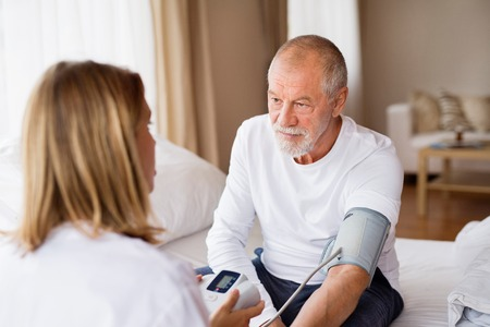 Gezondheid bezoeker en een senior man tijdens huisbezoek.