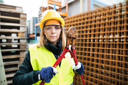 Young woman worker with large bolt cutters.