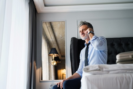 Mature businessman with a smartphone in a room. Stock Photo