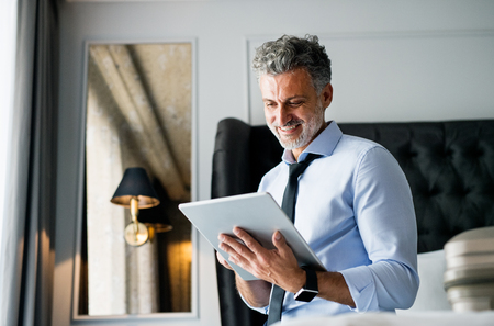 Mature businessman with tablet in a hotel room.