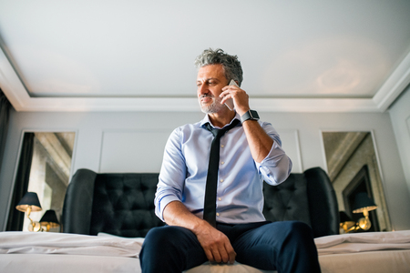 Mature businessman with smartphone in a hotel room. Stock Photo - 90147966