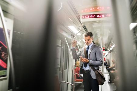 地下鉄の電車でスマート フォンで成熟した実業家。