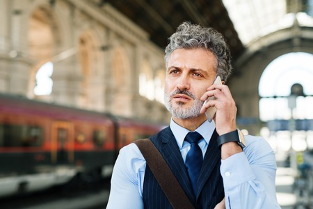 waiting phone call: Mature businessman with smartphone on a train station. Stock Photo