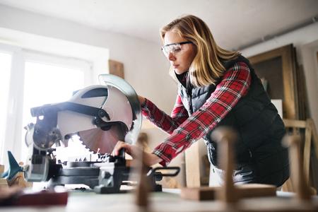 Jonge vrouwenarbeider in de timmermanswerkruimte. Stockfoto