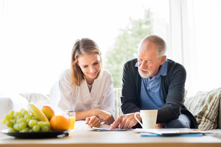 Health visitor and a senior man with tablet during home visit. Stockfoto