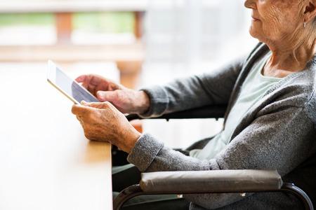 タブレットを自宅で車椅子で認識できない年配の女性。 写真素材