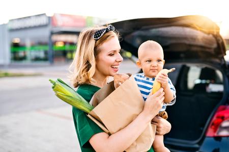 スーパー マーケットの前で男の子の赤ちゃんを持つ若い母親。