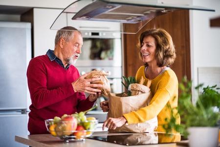 Senior couple preparing food in the kitchen.