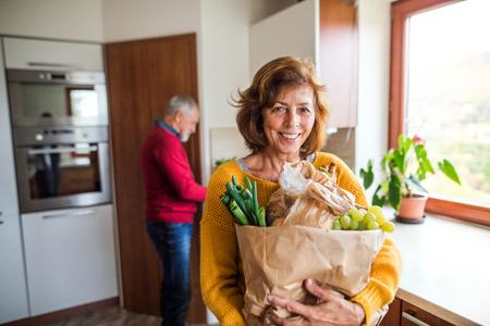 Hoger paar dat voedsel in de keuken voorbereidt.