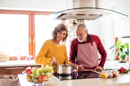Senior pareja preparando la comida en la cocina.
