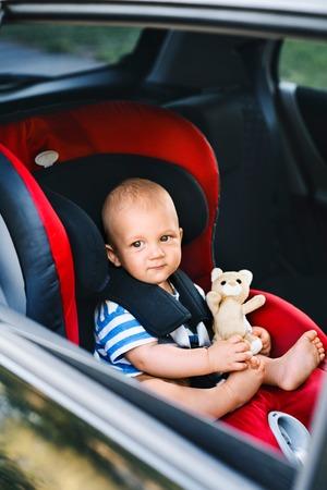 Kleine babyjongen zitten in de autostoel in de auto.