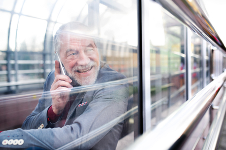 Senior man with smartphone in glass passage making phone call. Stockfoto