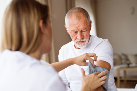Health visitor and a senior man during home visit. Stock Photo