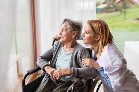 家庭訪問中の健康訪問者とシニア女性。