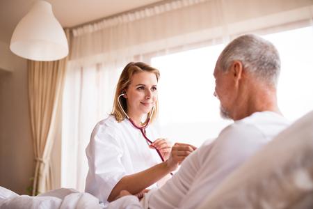 Visitatore di salute e un anziano durante la visita a casa. Archivio Fotografico
