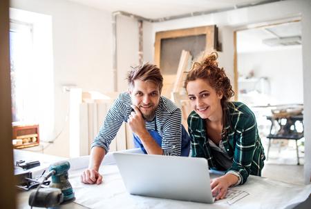 Junge Paare mit Laptop im Tischlerarbeitsraum.