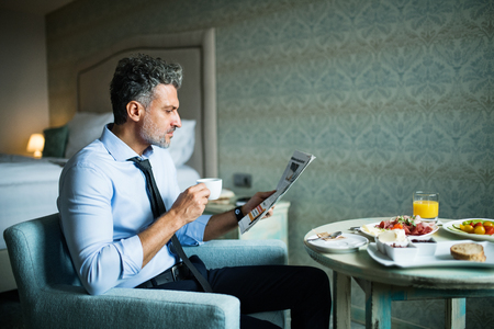 Mature businessman having breakfast in a hotel room. Stock Photo