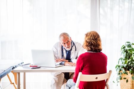 사무실에서 수석 여자에 게 얘기하는 노트북과 의사. 스톡 콘텐츠