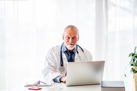 Senior doctor with laptop working at the office desk.