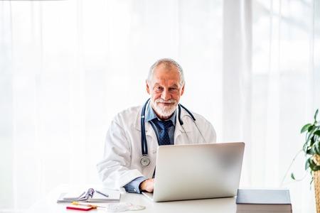 Hogere arts met laptop die bij het bureau werkt.