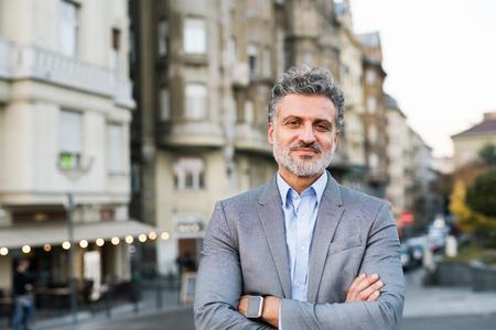 Rijpe zakenman met smartwatch in een stad.