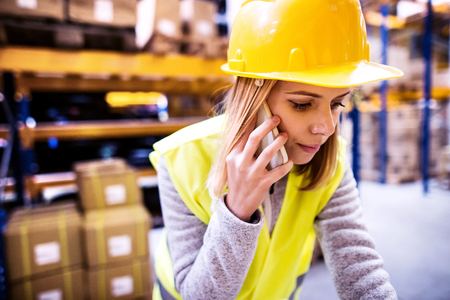 Female warehouse worker with smartphone. Stock Photo