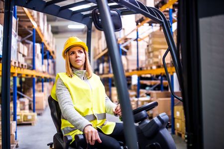 Woman warehouse worker with forklift. 版權商用圖片