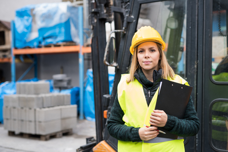 Woman forklift truck driver in an industrial area. Stock Photo - 91141763