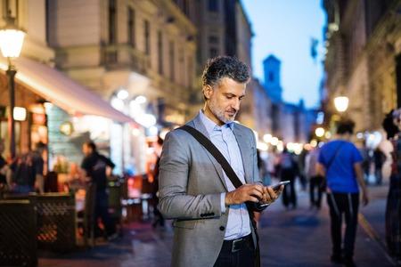都市でスマートフォンを持つ成熟したビジネスマン。