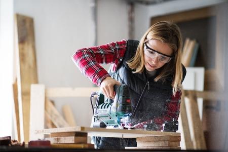Giovane lavoratrice nel laboratorio del carpentiere.