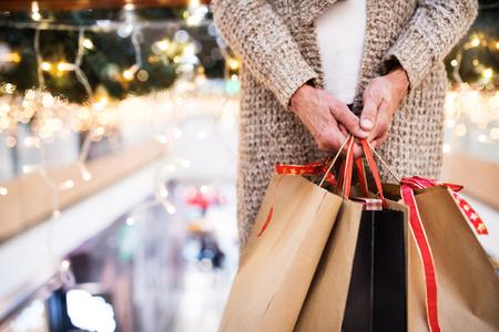 Ältere Frau mit Taschen , die Weihnachtseinkäufe kauft Standard-Bild