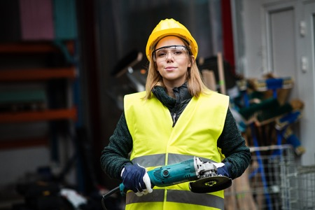 Woman worker with angle grinder in a warehouse. Stock Photo