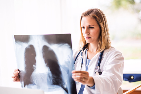 Female doctor with x-ray , working at the office desk. Stockfoto