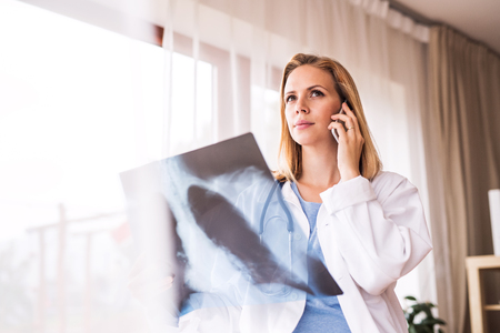 Female doctor with smartphone and x-ray. Stock Photo