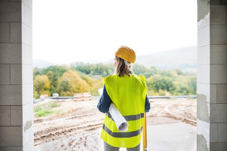 Jonge vrouwenarbeider op de bouwplaats.