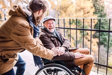 Lterer Vater im Rollstuhl und junger Sohn auf einem Spaziergang Standard-Bild - 91531039