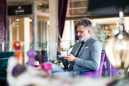 Mature businessman with coffee in a hotel lounge. Stock Photo - 91531383