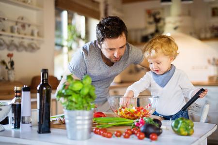 幼児の男の子の料理を持つ若い父親。 写真素材