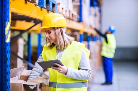 Woman warehouse worker with tablet. Banque d'images