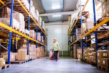 Woman warehouse worker with hand forklift truck. Banque d'images