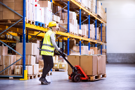 Woman warehouse worker with hand forklift truck. Stockfoto